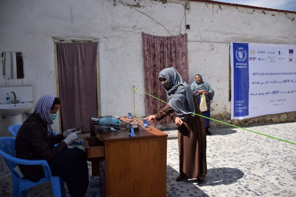 Afghanistan A woman receives cash assistance — from a safe distance.